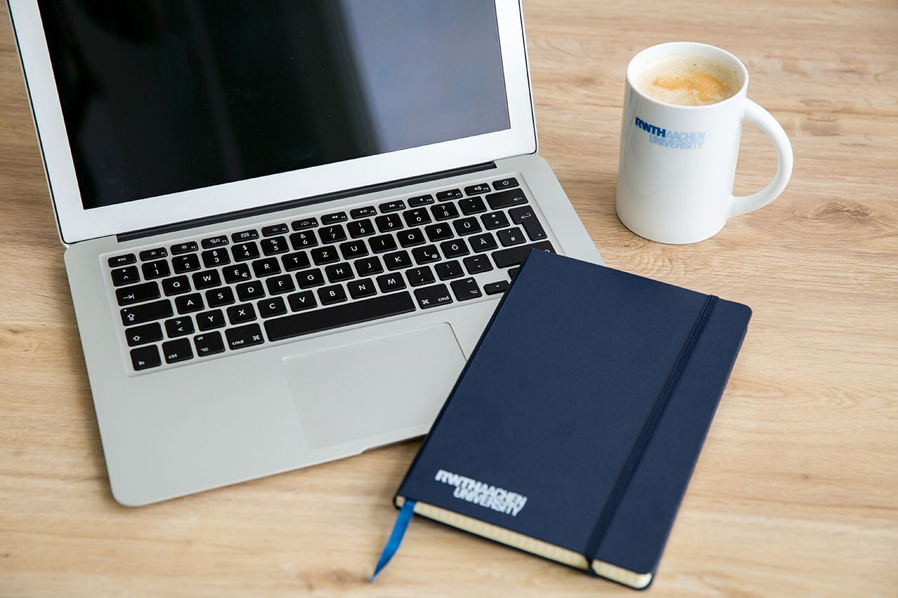A Laptop, a notebook and a coffee cup on a table top