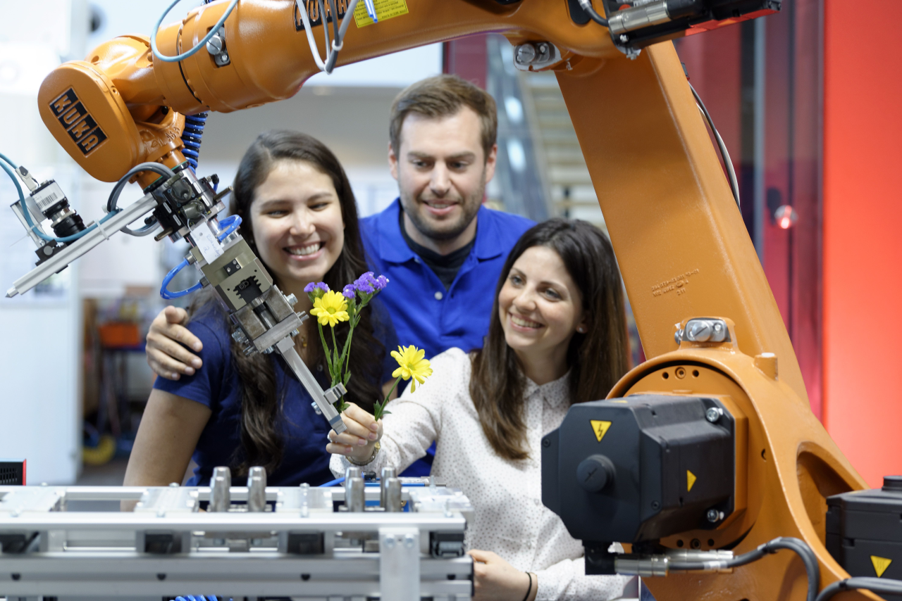 Individuals operating a robot arm