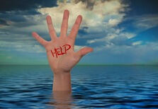 Photo of a hand rising out of the sea on which Help is standing