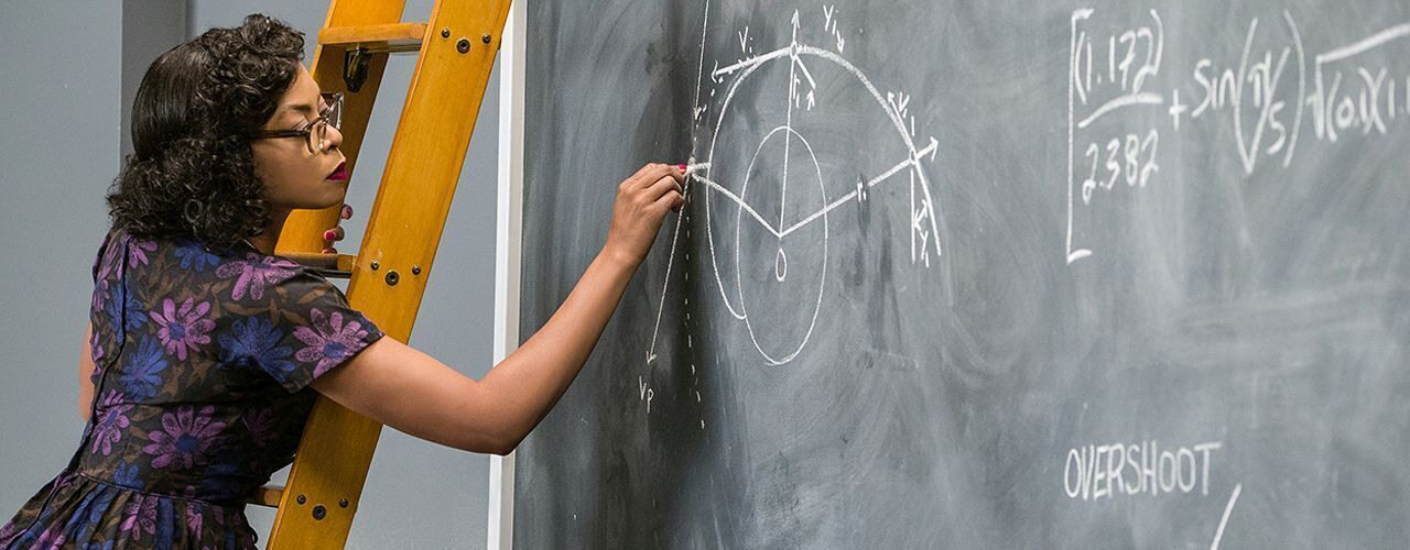 "A women is writing on a blackboard - a still from the film ""Hidden Figures"""